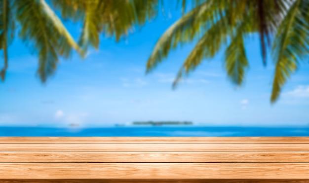 Tavolo in legno marrone sulla spiaggia tropicale estiva con spazio vuoto della copia sul tavolo per il modello di visualizzazione del prodotto