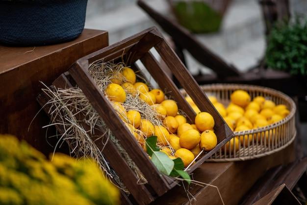 In una scatola di legno marrone, nella paglia ci sono limoni giallo arancio con rametti verdi. decorazioni fresche e vivaci per la decorazione della fiera del festival. succhi di frutta naturali. copia spazio