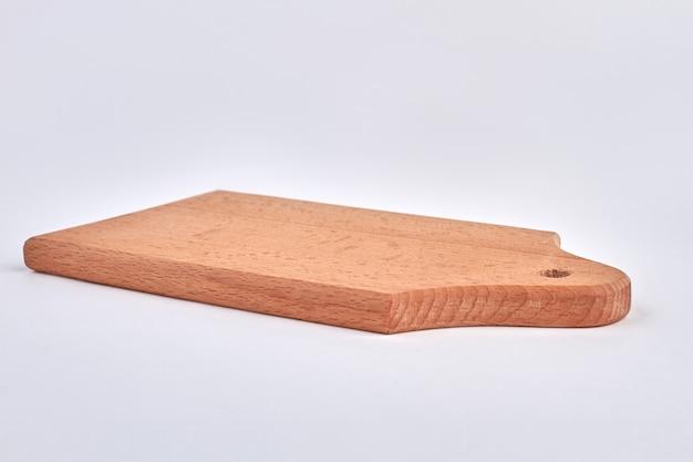 Tagliere di legno marrone isolato su bianco. utensile da cucina.