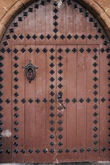 Una porta antica a doppia anta in legno marrone con rivetti in metallo e un grande anello battente nell'ovale