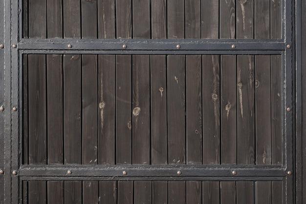 Cancello in legno marrone con strisce in metallo forgiato. sfondi e trame. avvicinamento