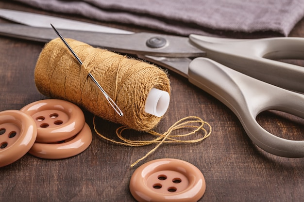 Sulla superficie di legno marrone ci sono oggetti da cucire.