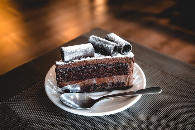 Brownie cake wite rotolo di cioccolato in cima mettere sul piatto di ceramica bianca con cucchiaino.