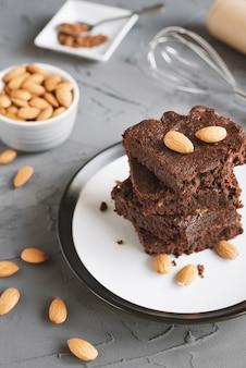 Torta brownie con noci di mandorle su sfondo di cemento