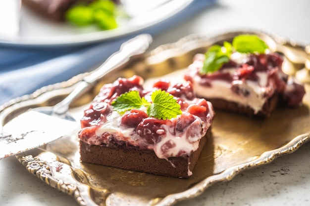Torte brownie alle ciliegie con panna, amarene e menta fresca su un vassoio vintage.