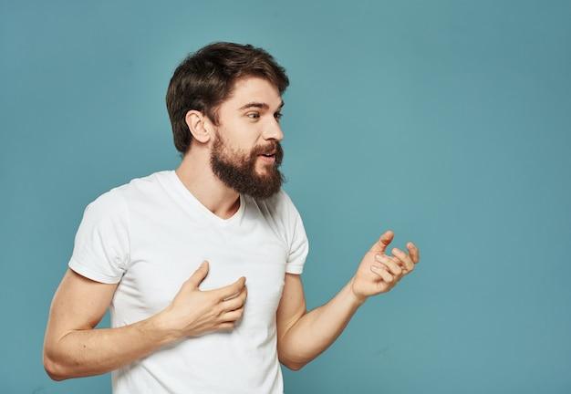 Uomo di brunet che gesticola con le sue mani in una maglietta bianca su un blu