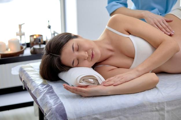 Bruna donna gravida asiatica che riceve un trattamento osteopatico nell'armadietto della spa in clinica. il terapista manuale manipola la pancia della donna, facendo con attenzione e professionalmente varie tecniche