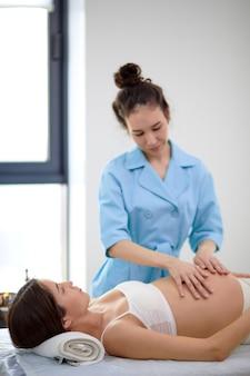 Bruna donna incinta asiatica che riceve un trattamento osteopatico nell'armadietto della spa in clinica. il terapista manuale manipola la pancia della donna, facendo con attenzione e professionalmente varie tecniche. vista laterale