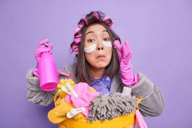 Bruna donna asiatica applica cerotti di bellezza sotto gli occhi rende l'acconciatura perfetta indossa vestaglia guanti di gomma tiene detersivo fa il bucato a casa fa casa