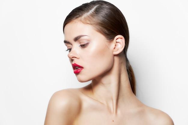 Vista ritagliata delle labbra rosse di fascino di sguardo laterale della pelle chiara delle spalle nude del brunette