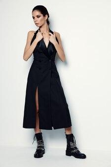 Bruna in un vestito nero e stivali su una leggera tuta da parete