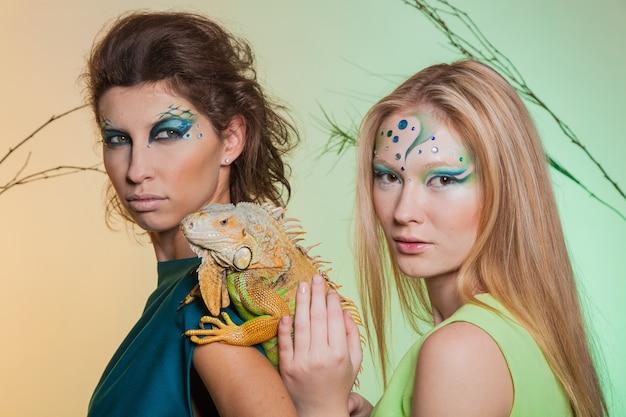 Bruna e bionda con un'iguana predatore tra le mani. immagine di un predatore femmina e una ragazza gentile con un animale in cattività