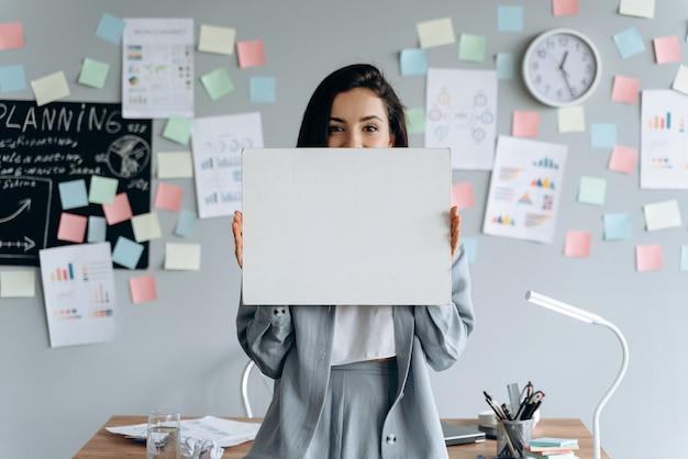 Bruna, ragazza di affari che tiene un pezzo di carta bianco e bianco su un muro grigio, adesivi