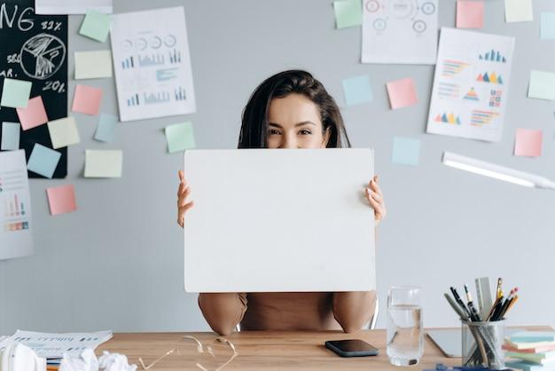 Bruna, ragazza di affari che tiene un pezzo di carta bianco e bianco su un muro grigio