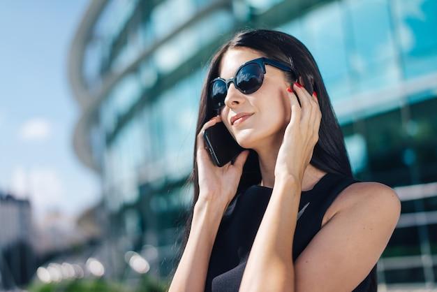 Donna d'affari brunetta che indossa un abito nero elegante e occhiali da sole in piedi davanti all'edificio in vetro hi-tech del centro business parlando sul suo telefono cellulare