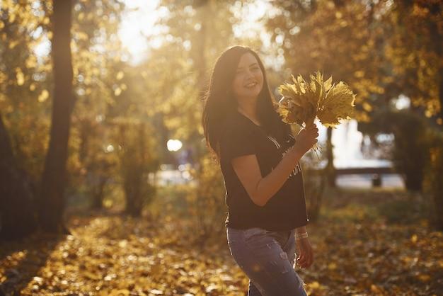 Bruna in abiti casual si diverte con le foglie nel bellissimo parco autunnale.