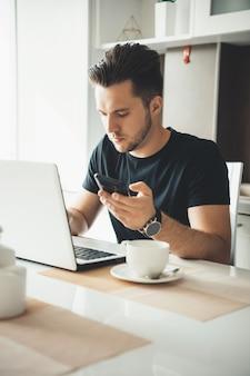 Uomo d'affari caucasico brunetta con setola che lavora da casa al laptop e in chat sul cellulare
