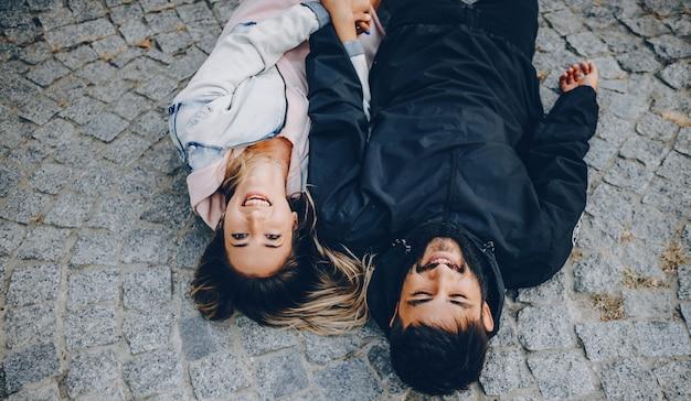 Bruna coppia caucasica sdraiata su uno sfondo di pietra e sorridente allegramente