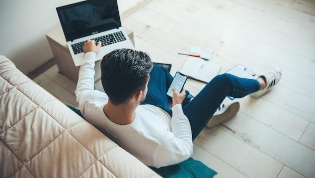 Uomo caucasico brunetta sta lavorando al laptop mentre guarda lo schermo del suo telefono seduto sul pavimento a casa e lavora con i documenti