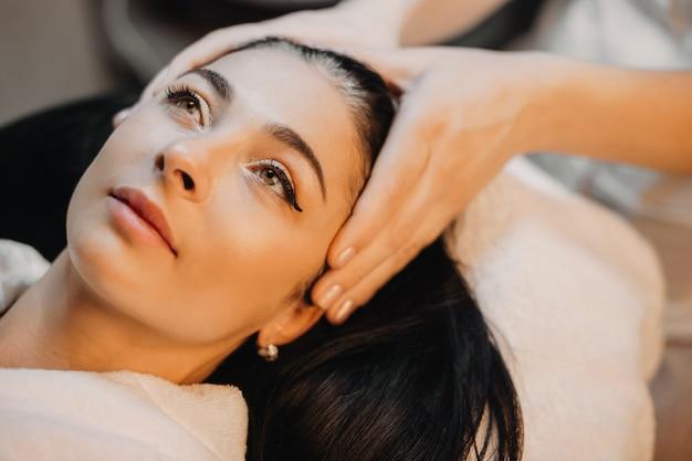 Donna caucasica castana che si trova durante un massaggio alla testa presso il salone della stazione termale