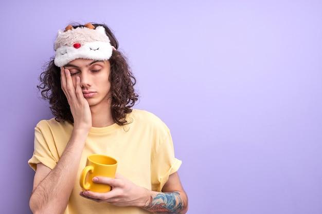 Bruna capelli ricci uomo caucasico non ha abbastanza sonno, vuole andare a letto la mattina, vestito casualmente con maschera per dormire, tenendo in mano una tazza gialla