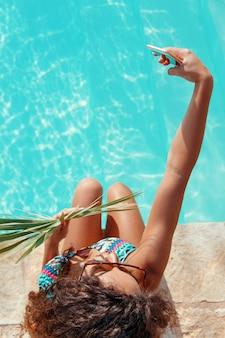 Giovane donna castana dei capelli ricci in costume da bagno intero che prende selfie con foglia tropicale sul bordo di una vista dall'alto della piscina