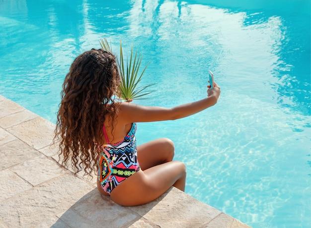 Giovane donna castana dei capelli ricci in costume da bagno intero che prende selfie con foglia tropicale sul bordo di una piscina