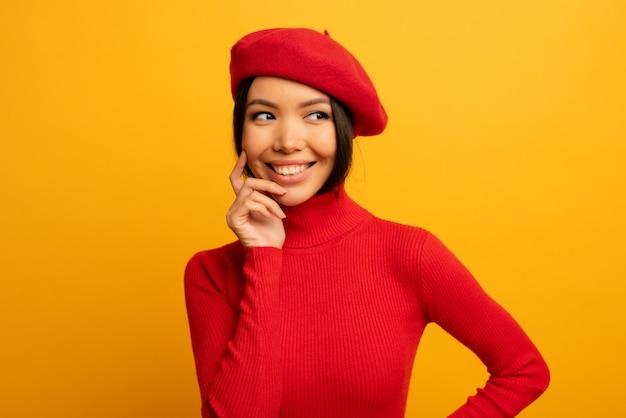 Sorrisi di ragazza carina bruna con cappello rosso e cardigan