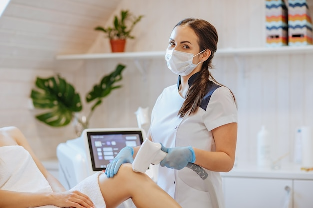 Bruna medico in guanti medicali blu e maschera che tiene una macchina per la depilazione e usandola sulle gambe della donna