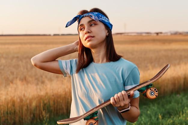 Donna bruna dall'aspetto piacevole che indossa maglietta blu e fascia per capelli, tiene lo skateboard in mano, distoglie lo sguardo, tiene il palmo sulla testa, tramonto sul campo.