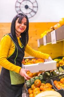 Bruna ragazza di frutta che lavora ordinare frutti in uno stabilimento di fruttivendolo, foto verticale
