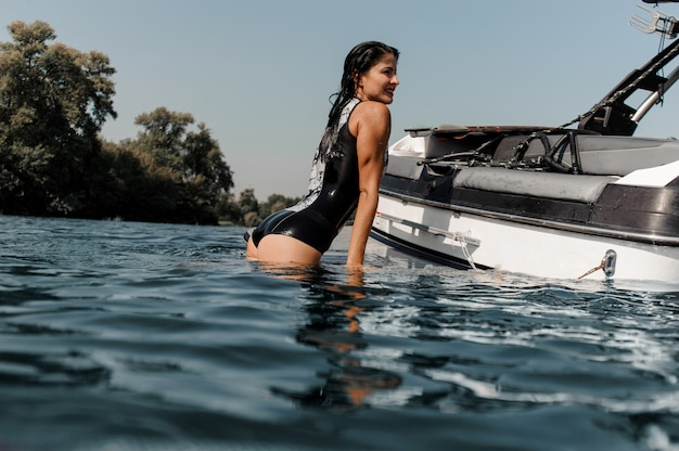 Ragazza bruna arrampicata sul motoscafo sul lago