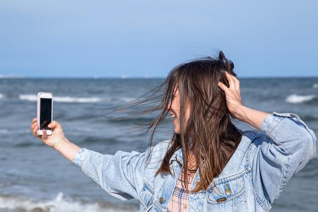 Ragazza bruna in una giacca di jeans fa una foto su un telefono con fotocamera selfie sullo sfondo del mare. concetto di viaggio e nuove esperienze.