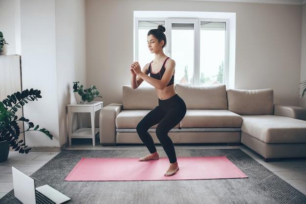 Ragazza bruna facendo esercizi di riscaldamento a casa su un tappeto sportivo rosa con un computer portatile