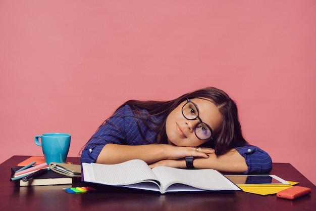 Ragazza bruna in occhiali e abito grigio blu seduto al tavolo con grande taccuino, tablet, matite, telefono e tazza blu, mettendo la testa sulle sue mani