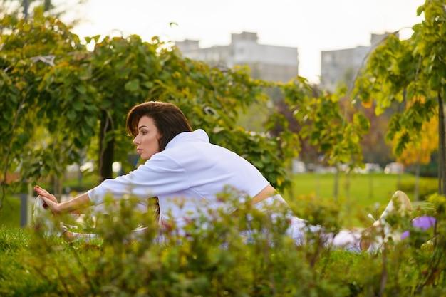 Ragazza bruna che fa fitness allenamento mattutino nel bellissimo parco verde naturale, seduta su un tappetino con spago e mani elastiche