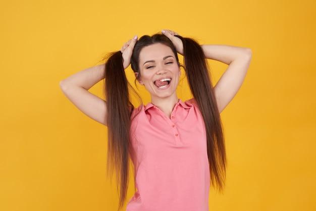 Ragazza castana che tiene allegro i capelli su giallo.