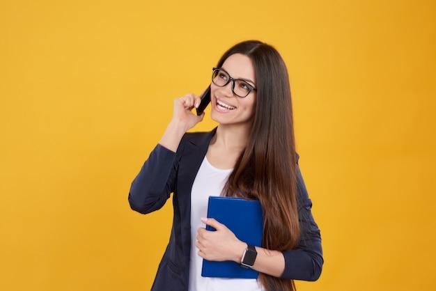 La ragazza castana posa la conversazione sul telefono su giallo.