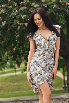 Ragazza bruna in posa in una strada di città donna d'affari piuttosto bella in abito elegante sullo sfondo della città