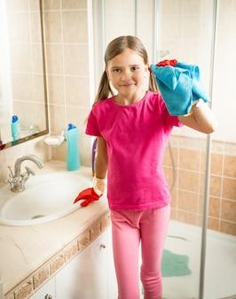 Ragazza bruna in posa con un panno blu mentre pulisce il lavandino in bagno