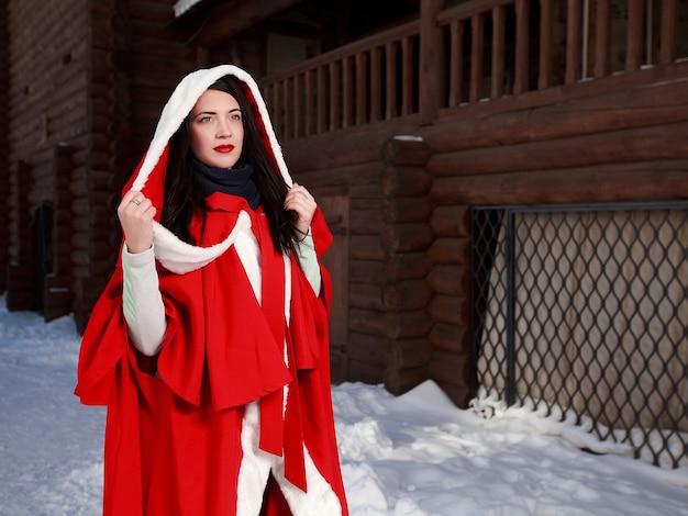Ragazza bruna in un mantello rosso inverno con edificio in legno sullo sfondo