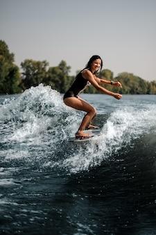 Ragazza castana che guida sul wakeboard sulle ginocchia di piegamento