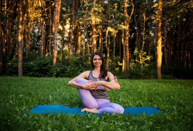 Una ragazza bruna si siede su una stuoia in un parco ed esegue yoga