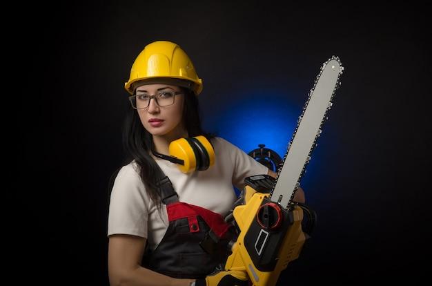 La ragazza bruna in abiti speciali e un lavoratore con un casco in posa su uno sfondo nero con uno strumento di lavoro (sega elettrica)