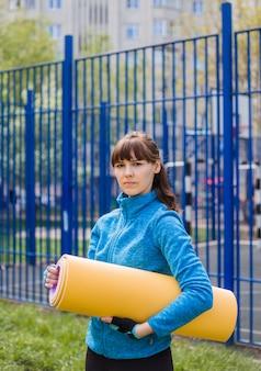 Una ragazza bruna in abiti sportivi con una stuoia per gli sport all'aria aperta. giacca sportiva blu e tappetino yoga giallo. uno stile di vita sano.