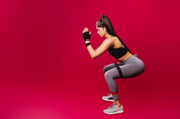 Ragazza bruna in abiti sportivi con benda elastica facendo esercizi su uno sfondo rosso con lato vuoto