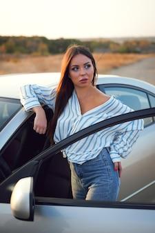 Ragazza castana in una camicia a righe e jeans vicino alla macchina