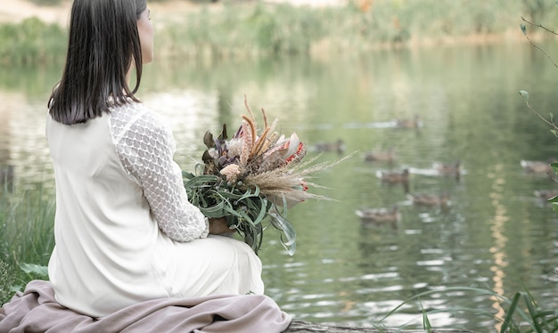 Una ragazza bruna in abito bianco si siede in riva al fiume con un mazzo di fiori esotici, sfondo sfocato, vista posteriore.