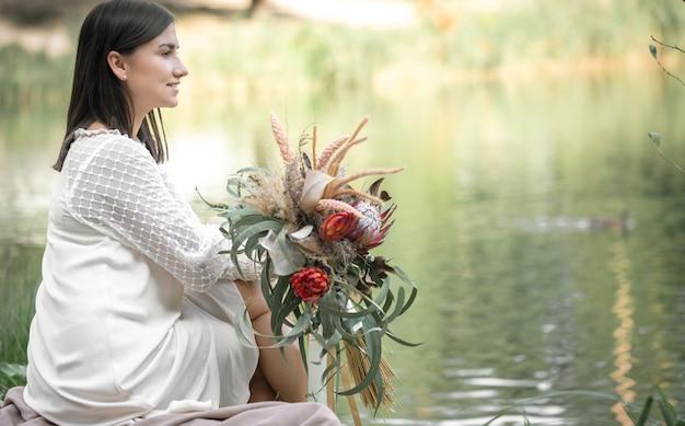 Una ragazza bruna in abito bianco si siede in riva al fiume con un mazzo di fiori esotici, sfondo sfocato.
