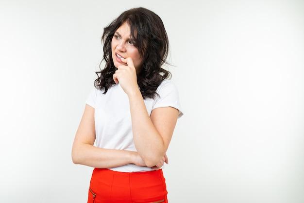 La ragazza castana in una maglietta bianca si preoccupa e morde le unghie dallo stress su un fondo bianco